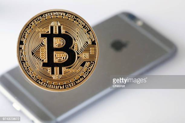 In this photo illustration a visual representation of the Bitcoin Digital Cryptocurrency sits on display in front of an Apple iPhone 6 on June 14...