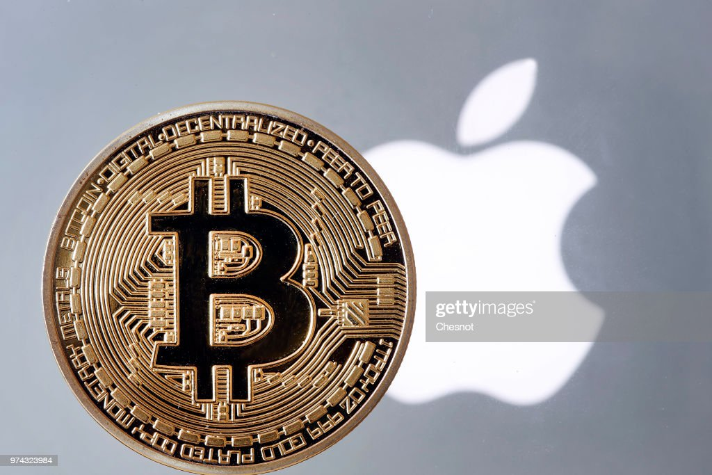 In this photo illustration, a visual representation of the Bitcoin Digital Cryptocurrency sits on display in front of an Apple logo on June 14, 2018 in Paris, France. Apple will now ban from the mobile App Store any applications of its iPhones that mines cryptocurrencies. According to AppleInsider, the new guidelines of the App Store clearly prohibits the exploitation of an iOS device in order to mine cryptocurrencies.