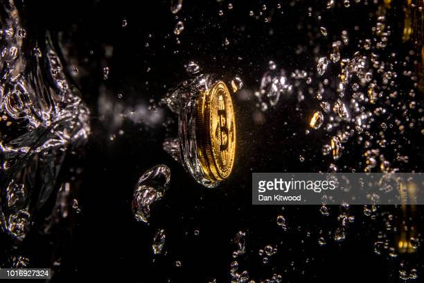 In this photo illustration a visual representation of the digital currency Bitcoin sinks into water on August 15, 2018 in London, England. Most...