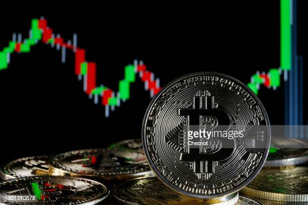 In this photo illustration, a visual representation of the digital Cryptocurrency, Bitcoin is on display in front of the Bitcoin course's graph on...