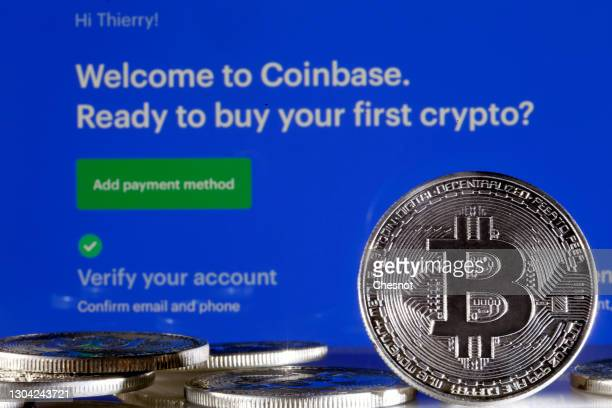 In this photo illustration, a visual representation of the digital Cryptocurrency, Bitcoin is displayed in front of the Coinbase cryptocurrency...
