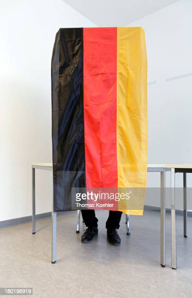 In this photo illustration a voter at a polling booth featuring the German national flag at the the local polling station in Friedrichshain a staged...
