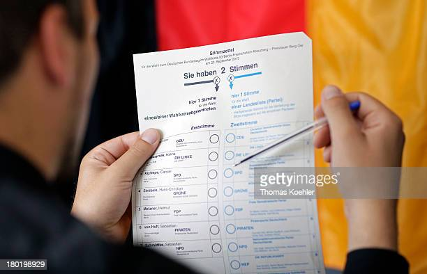 In this photo illustration a voter makeshis choice in the polling booth featuring the German national flag as blurred background at the the local...