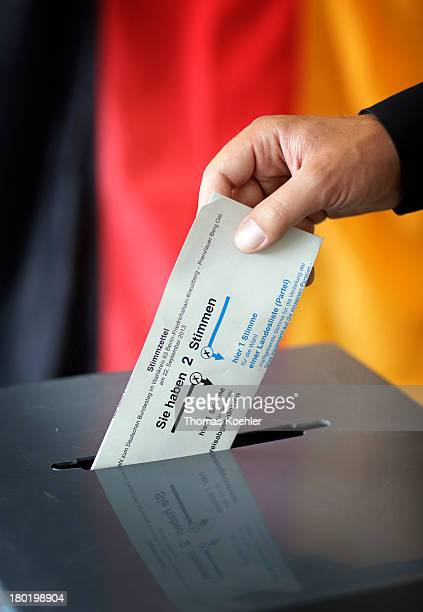 In this photo illustration a voter puts his completed ballot paper into the ballot box in the polling station at the local polling station in...