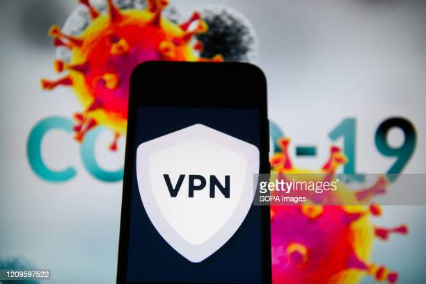 In this photo illustration a VPN logo is seen displayed on a smartphone with a COVID 19 sample on the background.