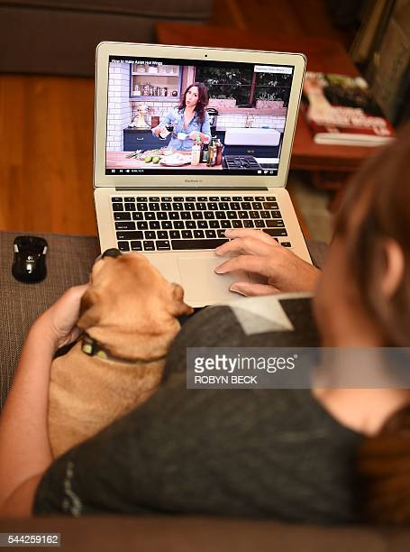 In this photo illustration a woman and a dog watch a video by chef and YouTuber Caroline Artiss on her YouTube page July 2 2016 in Los Angeles...