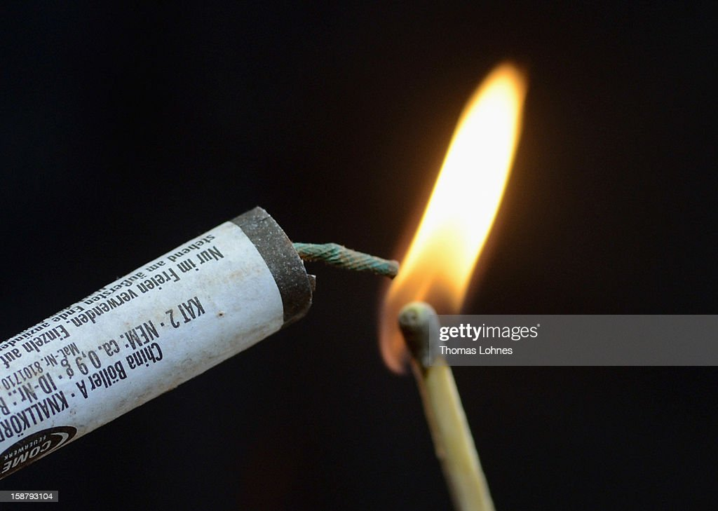 In this photo illustration a woman holds a burning matchstick and fireworks ahead of New Year's Eve celebrations on December 29, 2012 in Frankfurt, Germany. Fireworks sales are prohibited in Germany except for the three days before the new year, and both public and private fireworks displays are a central part of New Year's Eve celebrations.