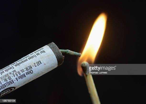 In this photo illustration a woman holds a burning matchstick and fireworks ahead of New Year's Eve celebrations on December 29 2012 in Frankfurt...