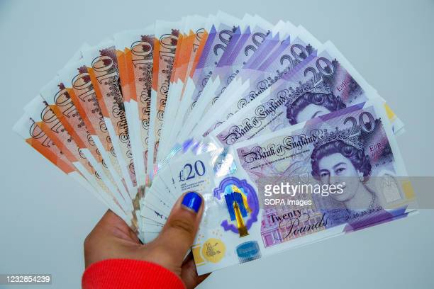 In this photo illustration, a woman holds a collection of British twenty pound sterling banknotes.