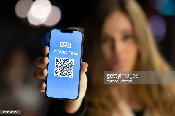 In this photo illustration a woman holds an Apple iPhone showing a NHS Covid Pass on October 8 in Cardiff, Wales. A covid pass for nightclubs and...
