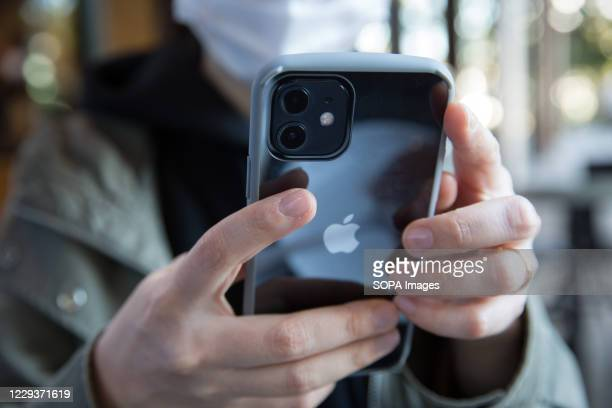In this photo illustration a woman holds the new iPhone 12 in her hands.