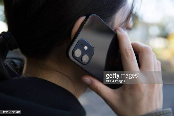 In this photo illustration a woman holds the new iPhone 12 in her hands while making a phone call.