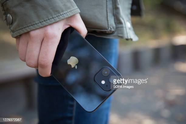 In this photo illustration a woman holds the new iPhone 12 in her hand.