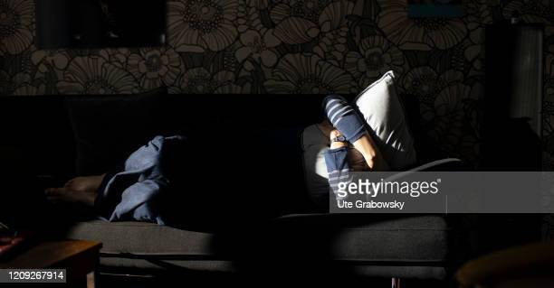 In this photo illustration a woman on a sofa is covering her face with a pillow on April 06 2020 in Bonn Germany