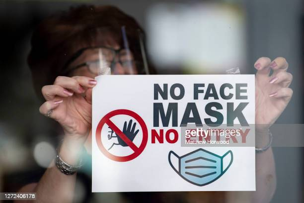 "In this photo illustration a woman puts a sign saying ""no face mask no entry"" in a shop window on September 14, 2020 in Newport, Wales. First..."