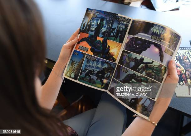 In this photo illustration a woman reads a copy of the Black Panther a fictional superhero appearing in comic book published by Marvel Comics in New...