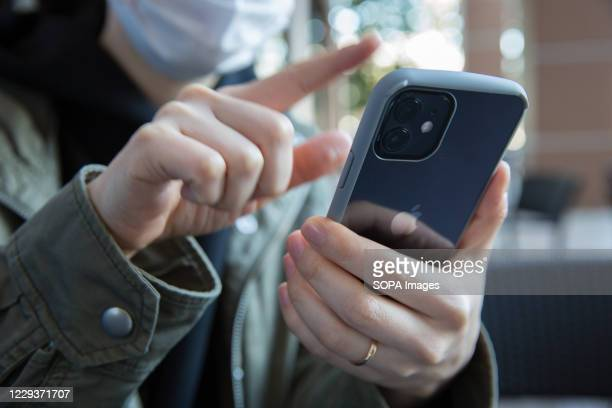 In this photo illustration a woman swipes with her finger on the screen of the new iPhone 12.