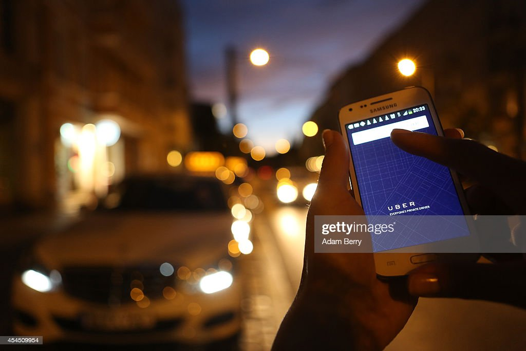 In this photo illustration, a woman uses the Uber app on an Samsung smartphone on September 2, 2014 in Berlin, Germany. Uber, an app that allows passenger to buy rides from drivers who do not have taxi permits, has had its UberPop freelance driver service banned in Germany after a complaint by Taxi Deutschland, a trade association of taxi drivers in the country. The company, which operates in 42 countries over 200 cities worldwide, plans to both appeal the decision made by a court in Frankfurt as well as, at the risk of heavy fines, continue its services in Germany until a final decision has been made on the matter.