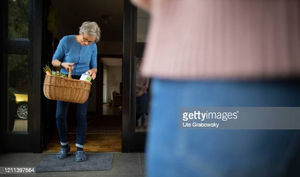 In this photo illustration a woman who is in quarantine controls the content of a basket of food on April 28, 2020 in Radevormwald, Germany.