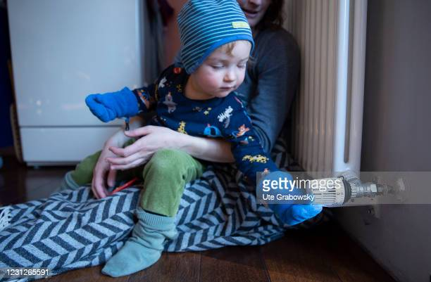 In this photo illustration a woman with a child sits in front of heater and turns thermostat on February 19, 2021 in Bonn, Germany.
