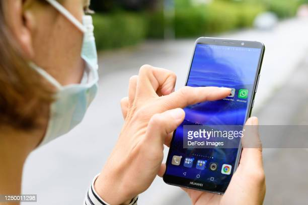 In this photo illustration A woman with a protective mask on is seen pressing her finger on the screen of her smartphone to open the Corona Warn app...