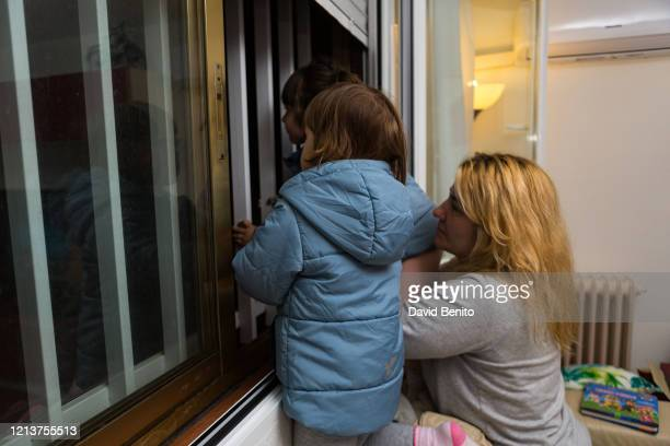 In this photo illustration a woman with her daughters applaud at 8 pm at the window of her house on March 20 2020 in Madrid The cases in Madrid are...