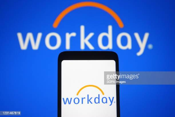 In this photo illustration a Workday logo is seen on a smartphone and a pc screen.