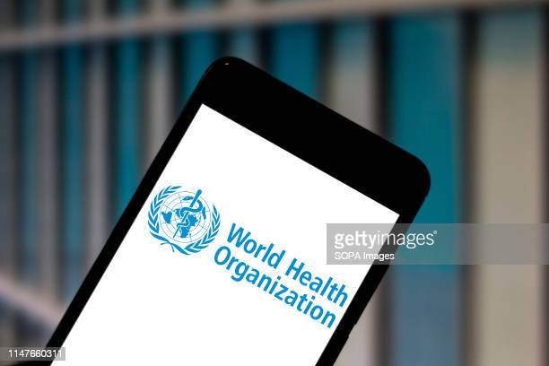 In this photo illustration a World Health Organization logo seen displayed on a smartphone