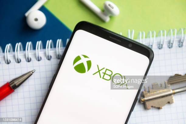 In this photo illustration, a XBOX logo seen displayed on a smartphone with a pen, key, book and headsets in the background.