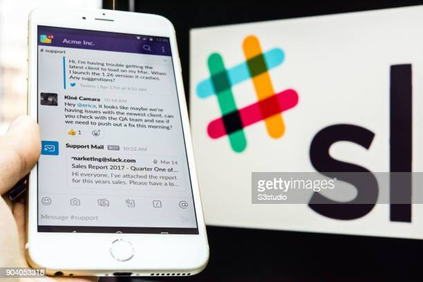 In this photo illustration, a young man is using an iPhone as he uses Slack on January 11, 2018 in Hong Kong, Hong Kong.