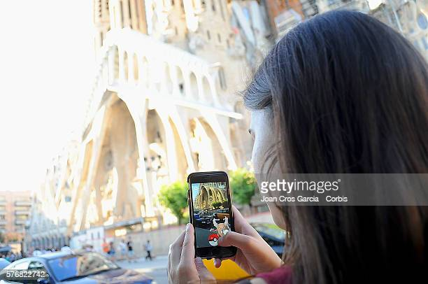 In this photo illustration a young woman plays Pokemon GO in front of Sagrada Familia on July 15 2016 in Barcelona Spain