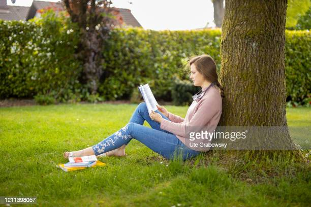 In this photo illustration a young woman sits on the lawn and reads in a book on April 28 2020 in Radevormwald Germany