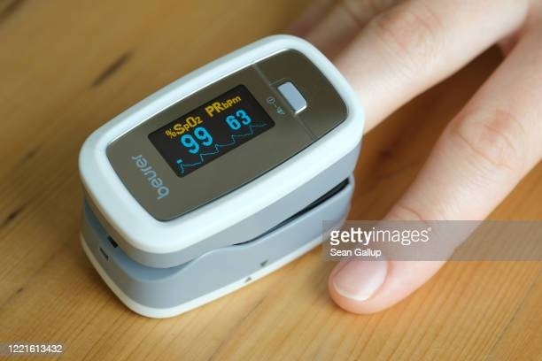 In this photo illustration, a young woman uses an oximeter to measure her pulse and her peripheral oxygen saturation level during the coronavirus...