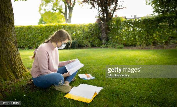 In this photo illustration a young woman wearing a mask sits on the lawn and reads in a book on April 28 2020 in Radevormwald Germany