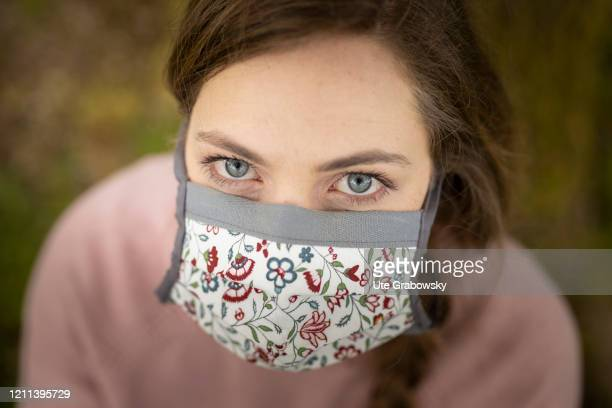 In this photo illustration a young woman wears a mask with a flower pattern to protect herself from the Corona pandemic on April 28 2020 in...