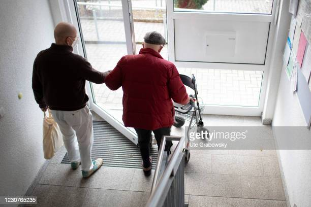 In this photo illustration a younger person accompany an old man with rolator on January 23, 2021 in Heidelberg, Germany.