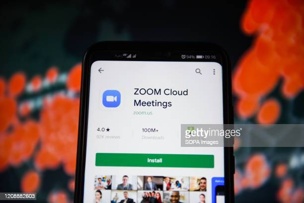 In this photo illustration a Zoom cloud meetings logo is seen displayed on a smartphone with a World map of COVID 19 epidemic on the background