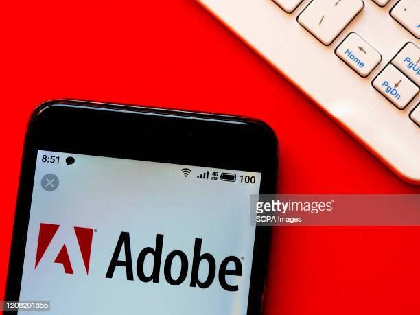 In this photo illustration an Adobe logo is seen displayed on a smartphone.