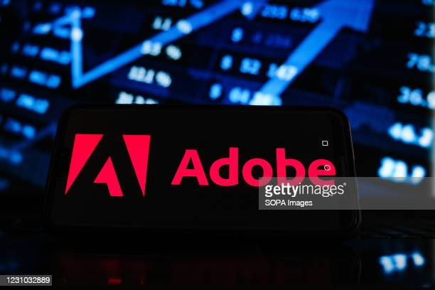 In this photo illustration an Adobe logo seen displayed on a smartphone screen with stock market graphic on the background.
