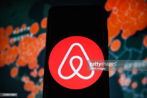 In this photo illustration an Airbnb logo is seen displayed on a smartphone with a World map of COVID 19 epidemic on the background.