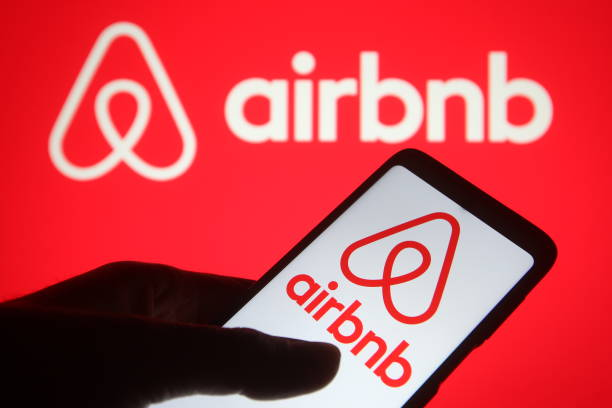 in this photo illustration an airbnb logo seen displayed on a and a picture