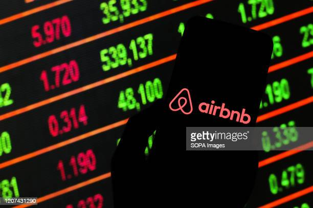 In this photo illustration an Airbnb logo seen displayed on a smartphone. Stock market prices in the background as stock markets tumble all over the...