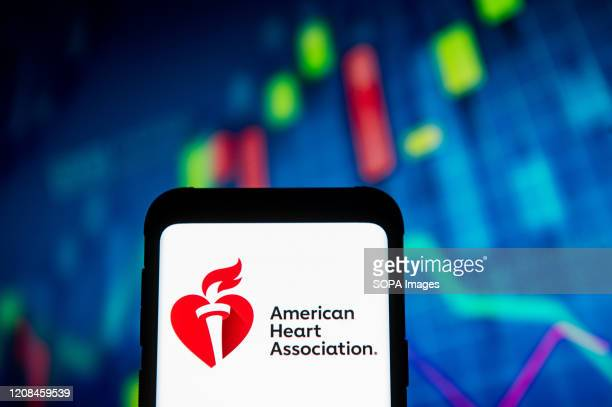 In this photo illustration an American Heart Association logo seen displayed on a smartphone A stock market chart is being displayed as the background