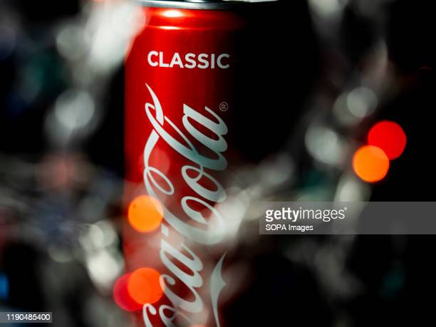 In this photo illustration an American multinational corporation and manufacturer of non alcoholic beverage CocaCola logo seen on can with blurred...