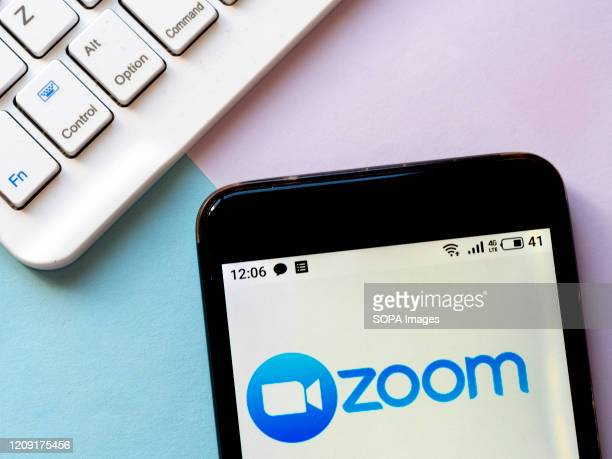 In this photo illustration an American remote conferencing services company, Zoom logo seen displayed on a smartphone.