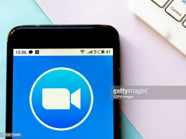 In this photo illustration an American remote conferencing services company Zoom logo seen displayed on a smartphone
