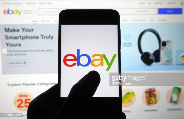 In this photo illustration an eBay logo seen on a smartphone screen in front of Ebay homepage.
