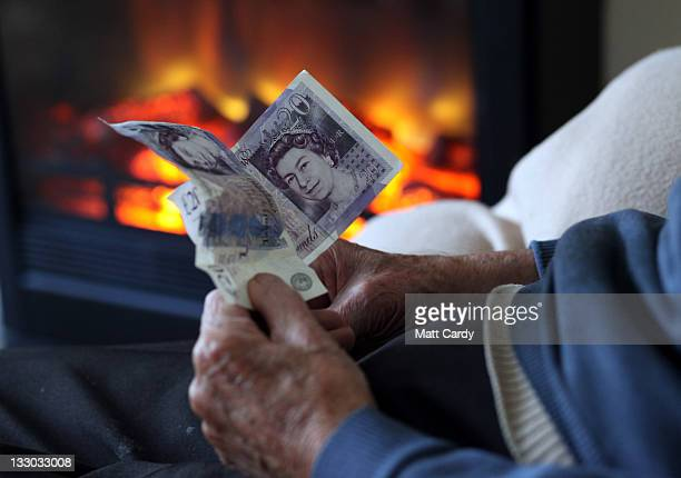 In this photo illustration an elderly man holds cash in his hands as he warms himself in front of a fire on October 6 2011 in Bristol England Energy...