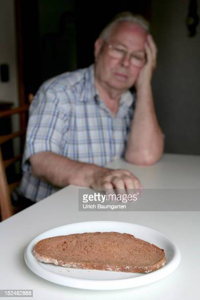 In this photo illustration an elderly man sits in the front a dry slice of bread for symbolizing oldage poverty on September 19 2012 in Koenigswinter...