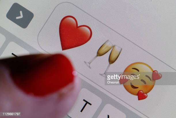 In this photo illustration an emoji or emoticon representing a heart a glass of champagne and heartshaped eyes are displayed on the screen of an...